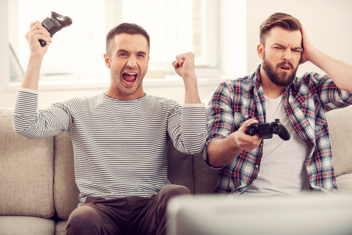 Two men playing video games with one happy and one disappointed.