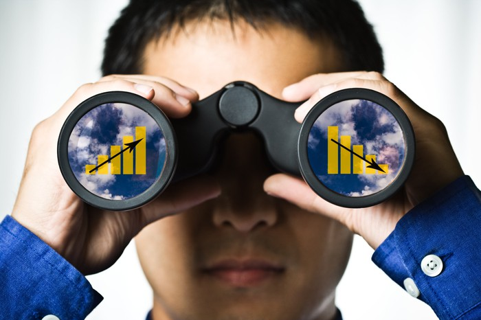 Man holding binoculars with charts in both lenses.