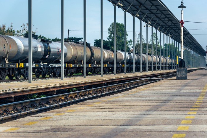 A row of tanker cars lined up outside a rail station.