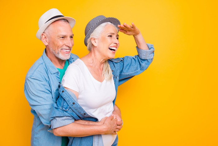 A senior couple wear cool thin bill hats and denim shirts as the woman looks into the distance against an orange background.