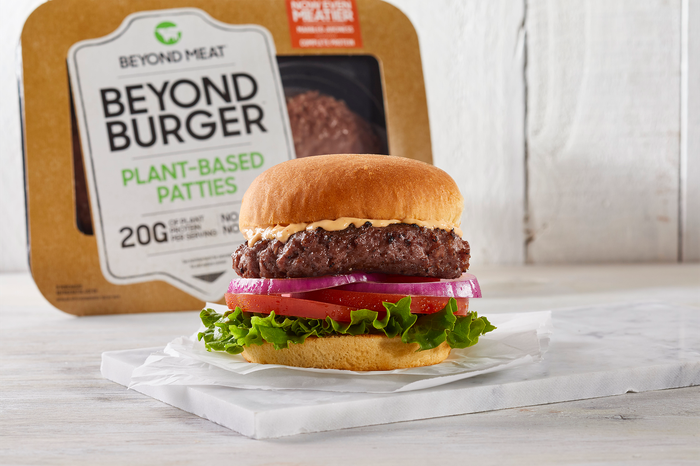 A Beyond Burger package behind a burger sitting on a chopping board.