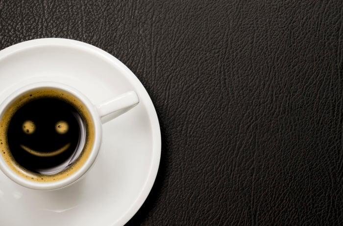 A smile drawn in the foam of an espresso.