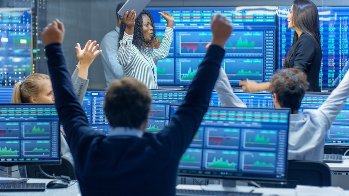 Traders celebrating in front of colorful monitors displaying stock market data.