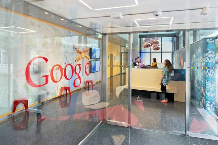 A plexiglass wall with the Google logo, near an office entrance.