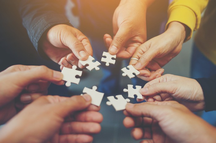 Seven people holding puzzle pieces.