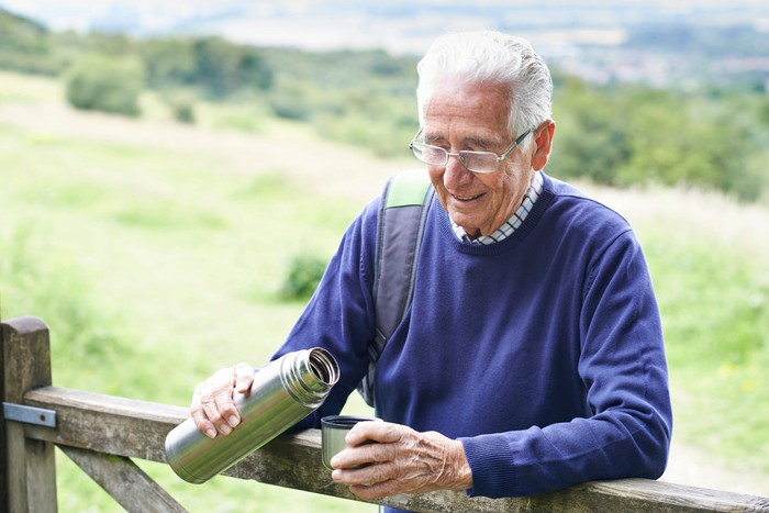 Senior man outdoors holding an open thermos