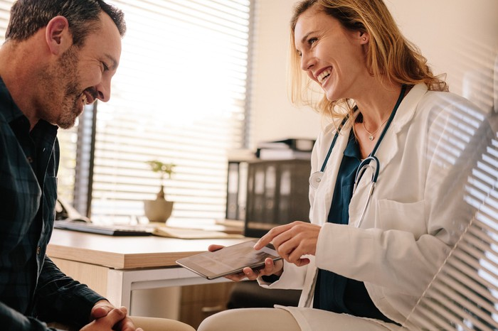Doctor using a tablet to show a patient his test results.