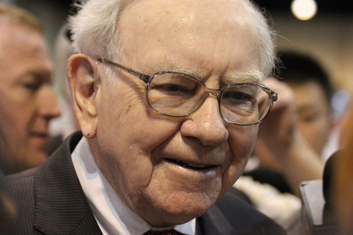 Warren Buffett smiling with a crowd of people behind him.