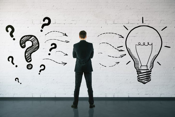 A businessman with his back to the camera staring at a drawing of question marks and a light bulb on the wall.