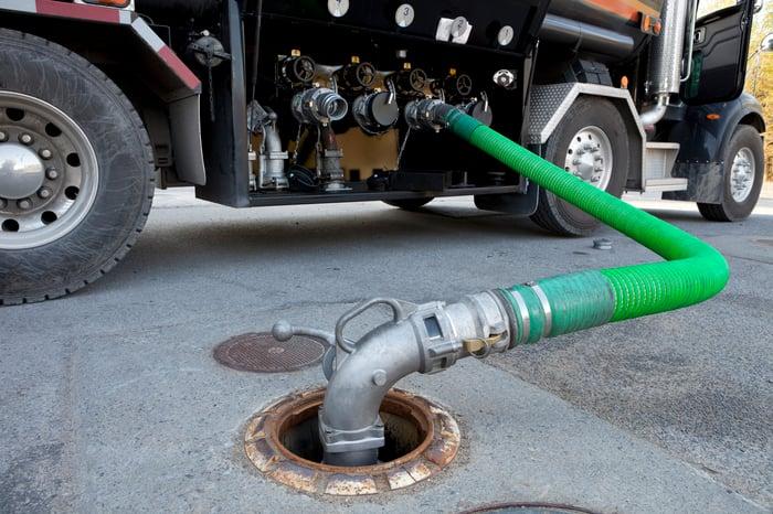 Fuel tanker delivering gasoline to a gas station.