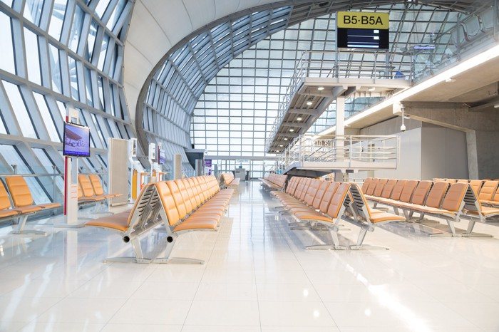 A modern airport terminal gate seating area, with comfortable seats and abundant natural light.