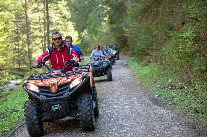 A group of people riding all-terrain vehicles down a narrow path in the forest.