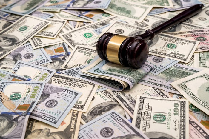 A judge's gavel on top of a pile of U.S. currency.