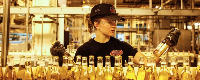 A beer factory worker inspecting bottles filled with beer.