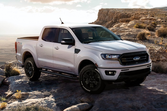 A white Ford Ranger perched on a rock
