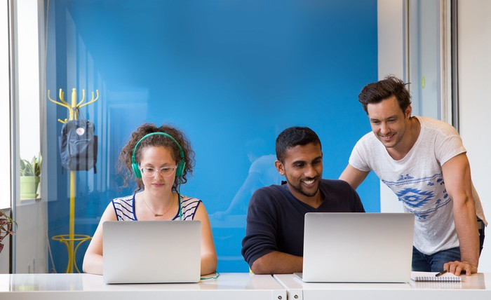 Employees at laptops in a Wix office