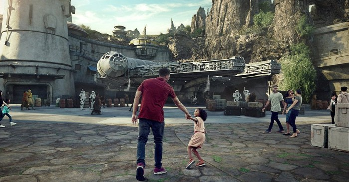 Concept art for Star Wars: Galaxy's Edge with a man and a young child in front of the Millennium Falcon.