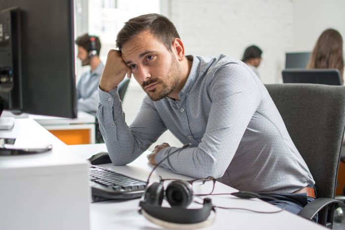 Man sitting at a computer with a serious expression, resting his head on his fist