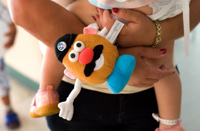 A woman's arms holding a small child and a plushie Mr. Potato Head.