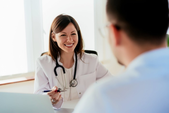 Man sitting across from smiling female doctor