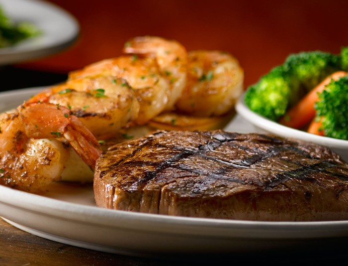 A plate with a steak, shrimp, and vegetables.
