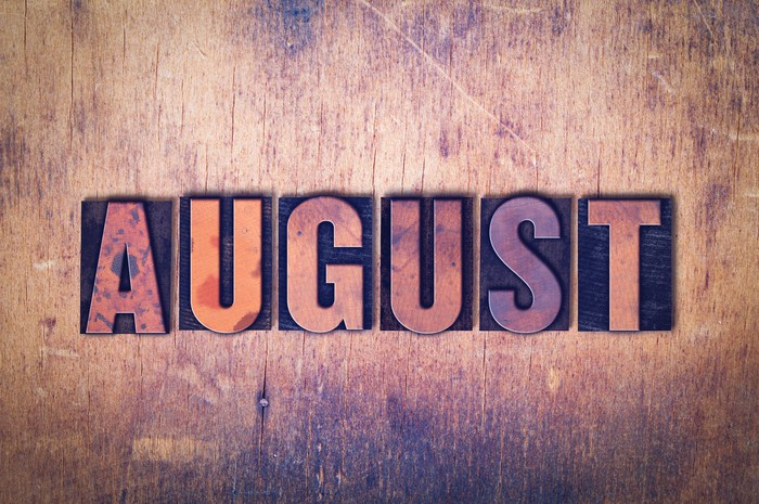 August spelled out in block letters on a wooden background.
