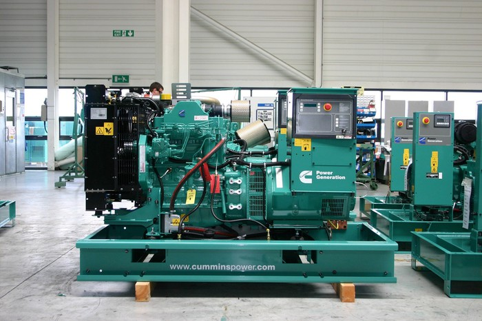Green power generation equipment in a warehouse, with Cummins logo on it.