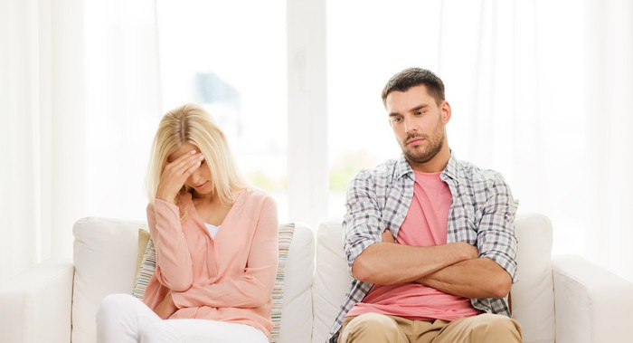 Two people sit on a couch looking angry and sad.