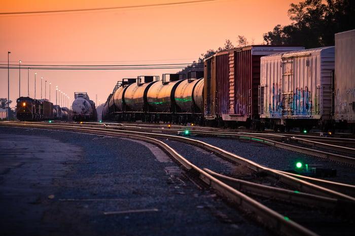 A freight train in a rail yard at dusk.