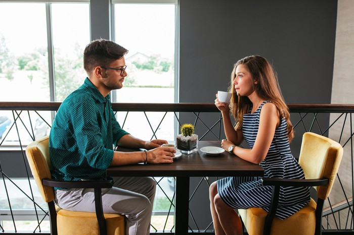 Man sitting across from woman at table