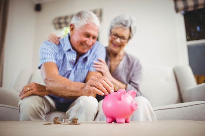 An older woman sits next to an older man putting a coin into a piggy bank.