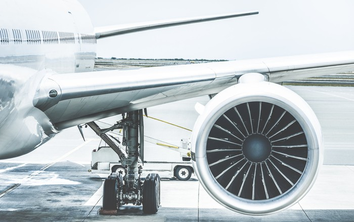 Detail of an airplane engine and wing at a terminal gate