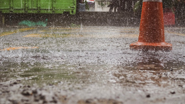 Rain falling near an orange cone.