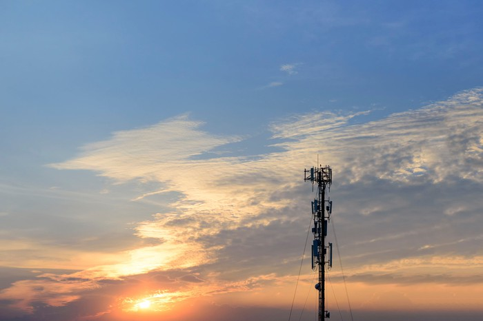 A cell tower with the sun setting in the background.
