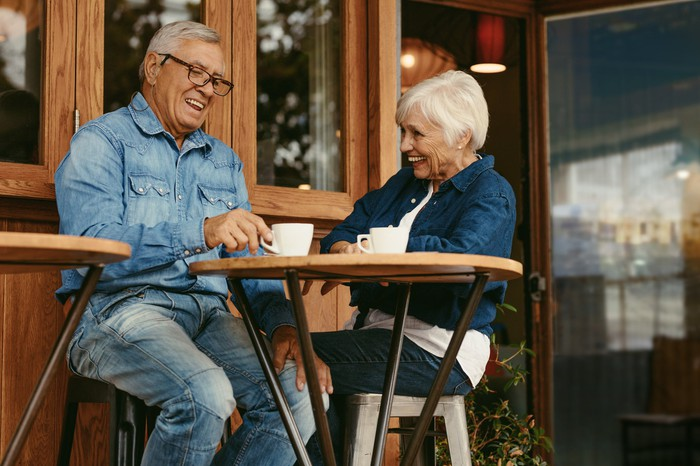 Older man and woman sitting at small table with mugs in front of them