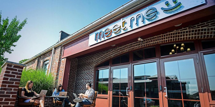 Three employees sitting outside of MeetMe's corporate office.