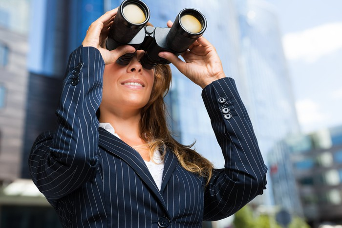 A woman wearing a striped suit jacket looks through a pair of binoculars.