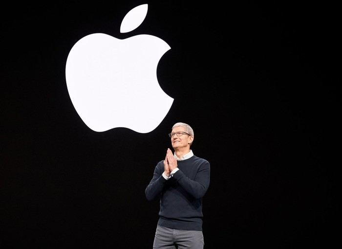 Apple CEO Tim Cook on stage with the Apple logo on the screen in the background.