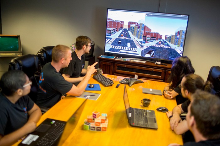 Quantum Signal employees seated at a table with a large screen at the end of the table displaying a simulation environment