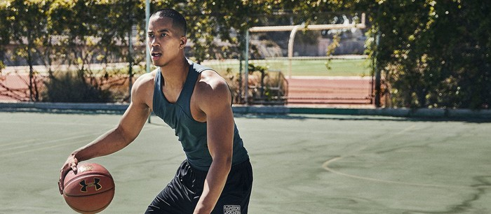 A man dribbling a basketball on a court while wearing Under Armour clothing.