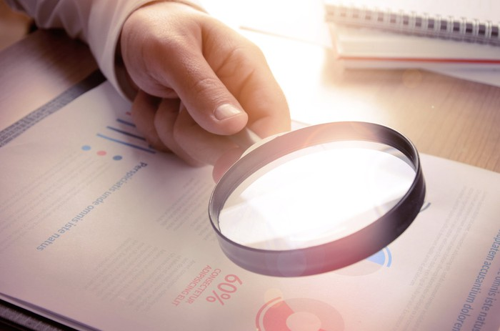 A person wearing a suit uses a magnifying glass to read a stock report.