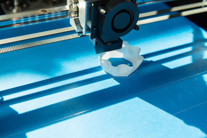 Close-up of a 3D printer with a blue surface printing a white plastic object.