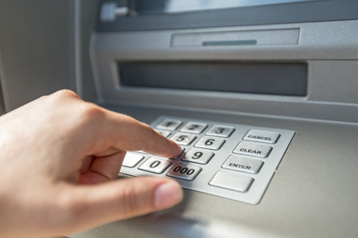 A person uses an ATM.