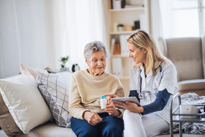 Nurse speaking with mature woman in her house about a medication