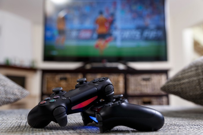 Two video game controllers on a carpeted floor in front of a large TV.