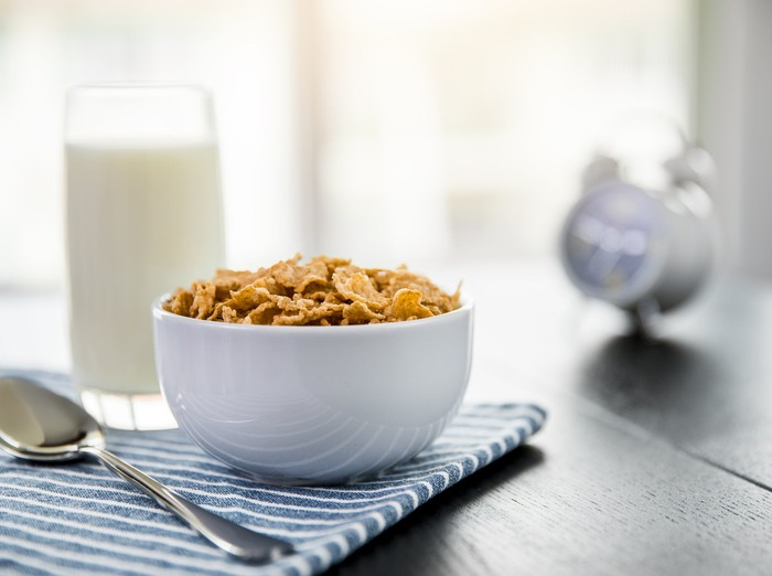 Bowl of cereal and glass of milk on a table