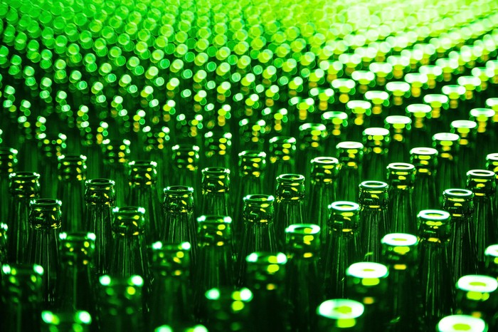 Table full of green glass bottles that have just been manufactured.