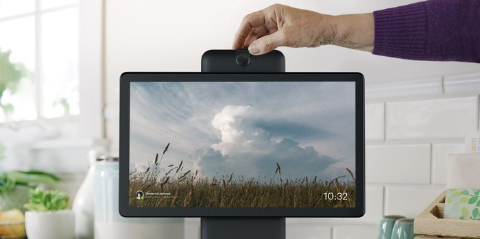 A person's hand positioning the camera atop a Facebook Portal device.