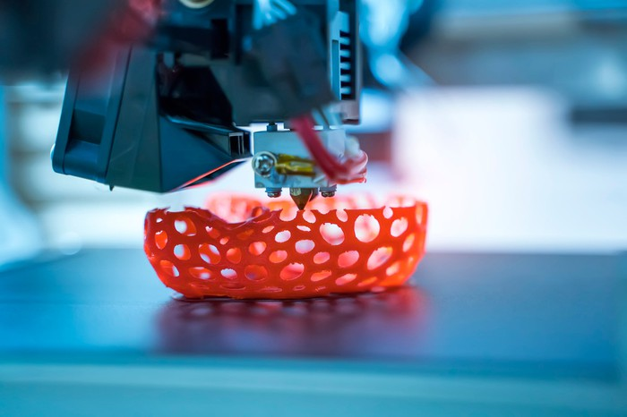 3D printer creating a sponge-like bowl shape with red-orange filament.