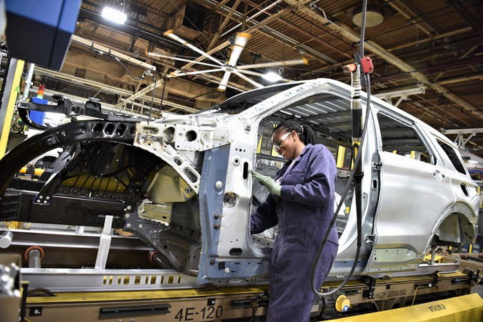 A worker at Ford's Chicago Assembly plant performs a task on a partially assembled 2020 Explorer SUV.